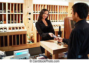 Shop - Man buys a bottle of wine in the store
