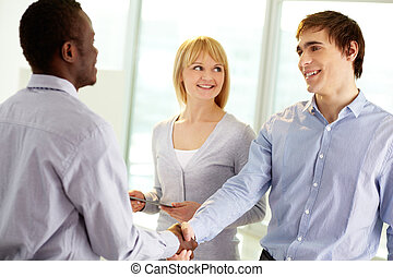 Greeting - Image of confident business partners handshaking...