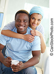 Sweethearts - Image of young African couple looking at...