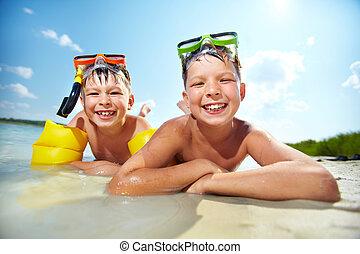 Siblings on beach - Photo of happy siblings lying on sand on...