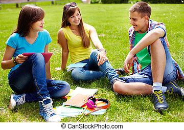 Homework outdoors - Cute high-school students doing homework...