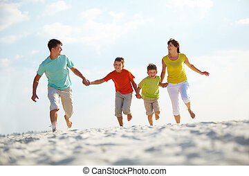 Family running - Photo of happy family running down the...