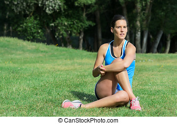 Woman Injury Prevention - Young female athlete stretching...