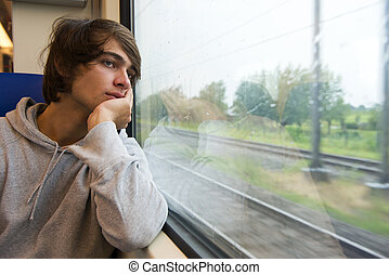 Traveling by train - Bored young man, staring out the train...