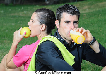 Sports Nutrition - Couple of athletes taking a break, eating...