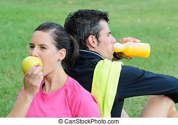 Ahtletes Nutrition - Couple of athletes taking a break,...