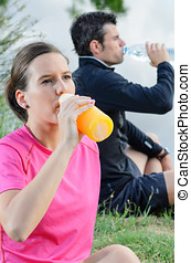 Athletes Hydration - Young couple of athletes sitting and...