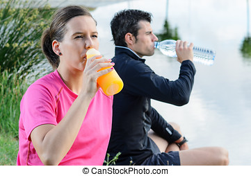 Couple Drinking - Young athletes sitting and drinking water...