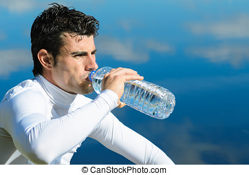 Athlete drinking - Handsome sportman drinking water on a...