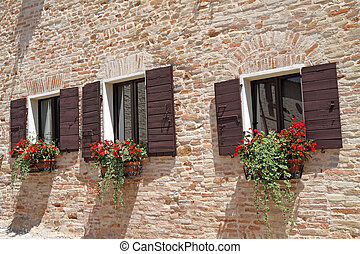 brick wall with windows with shutters and flowers in pots -...