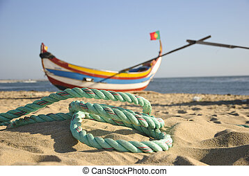 Old fishing boat with rope infront on the beach of Espinho,...