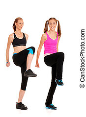 Two women doing zumba fitness on white background