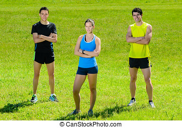 Athletes idly - Young athletes looking at camera with grass...