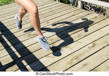 Woman Running Shadow - Legs and shadow of a young woman...