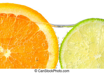 Orange and lime slices in water with air bubbles on white...