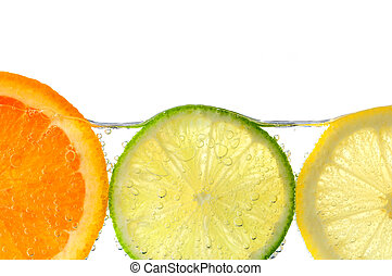 Orange lemon and lime slices in water with air bubbles on...