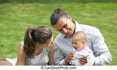 happy young family - young lovely parents playing with their...