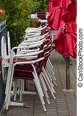 Street cafe chairs - Street cafe umbrellas and chairs on the...