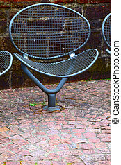 A public metal chair on the promenade in small city...