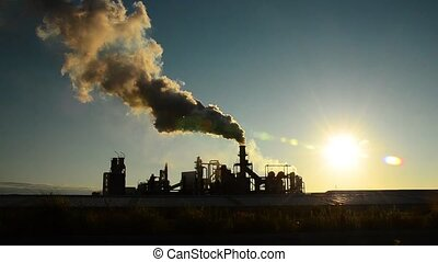 Smoke stack against the sunny sky - Fumes billow out of a...