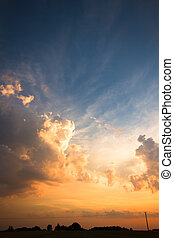 clouds - occurring yellow sun behind the clouds on a warm...