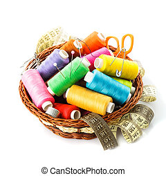 Sewing items in basket: threads, pins, meter and scissors on...