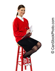 Girl sitting on high stool writing in notebook