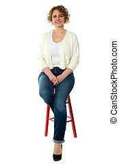 Confident smiling woman sitting on stool and looking at...
