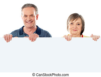Old age couple holding blank banner ad against white...