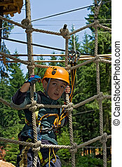 Happy boy in the adventure park - Happy boy climbing on rope...