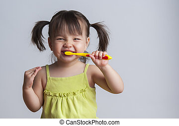 Girl brushing teeth - Toddler smiling while brushing her...