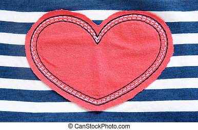 Red heart textile on a striped background, a horizontal...