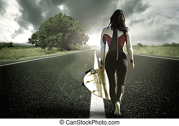 surfer girl walking down the beach road road