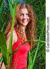 beautiful girl in red among high green grass of summer...