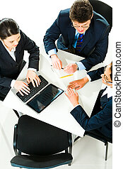 Business meeting - Photo of three business people sitting at...