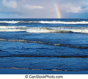 Ocean Waves Breaking on Shore with a Partial Rainbow in the...