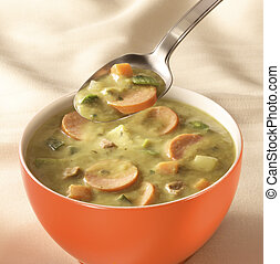 bowl of pea soup - bowl on a table with pea soup and a spoon...