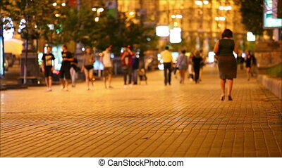 People walking down the street at nigh
