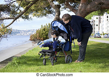 Father spending time with disabled son in wheelchair at the...