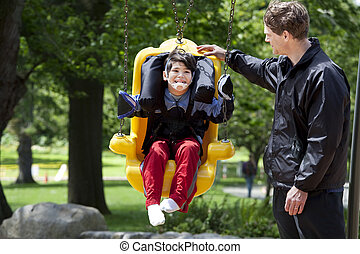 Father pushing disabled boy in special needs swing - Father...