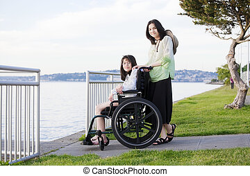 Taking care of sister in wheelchair by beach - Young teen...