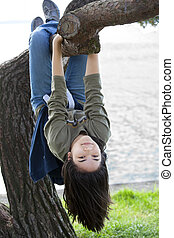 Young teen girl hanging upside down on tree limb