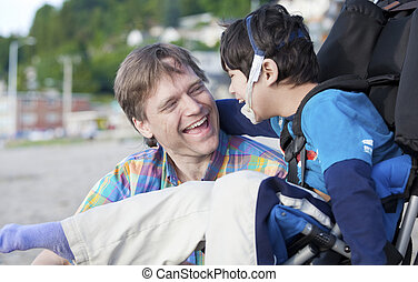 Father enjoying beach with disabled son - Father and...