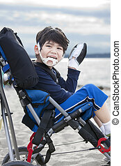 Happy disabled five year old boy in wheelchair on the beach