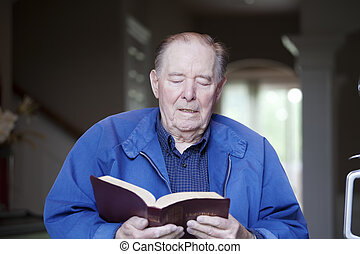 Elderly 90 yr old man reading the Bible