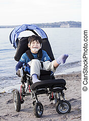 Happy disabled boy in wheelchair on the beach
