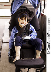Disabled little preschool boy in wheelchair on bus