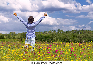 Man with arms wide open in the middle of the field