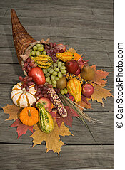 Cornucopia filled with fall harvest spilling out of it\\\'s...