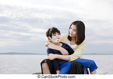 Teenage sister holding her disabled brother on the beach....
